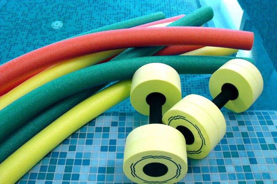 aqua noodles dumbbells for aqua aerobics lie on the coast in pool
